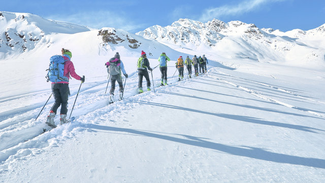 Group of touring skiers whit alpine guide reaching their goal