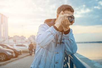 A man in a denim jacket with a vintage film camera at sunset