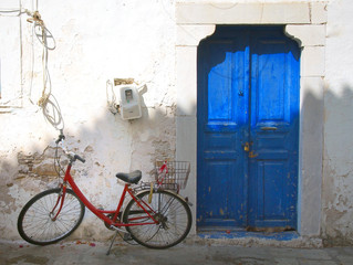 colourful summer scene of an old red bike outside a greek house with whitewashed walls and a blue painted door in bright sunlight in Kos