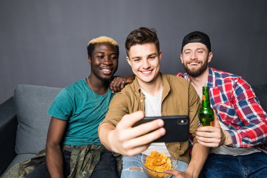 Portrait of stylish, best, attractive, modern positive guys with hairstyle, bristle sitting on couch, having mugs with lager in hands, shooting selfie on smart phone, enjoying, spending time