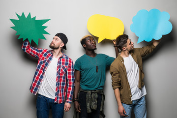 Three young mixed race men friends with speech bubbles isolated on gray background