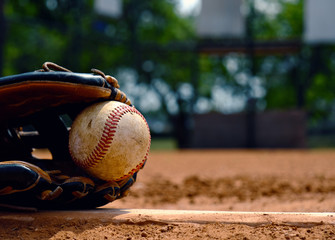 Baseball in glove laying on pitcher's mound of ball field.  Old used sports equipment for team sport.