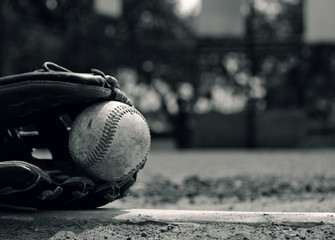 Baseball in glove laying on pitcher's mound of ball field.  Vintage style sport graphic in black and white.