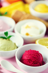 Red, purple, yellow, green, white ice cream balls in bowls, waffle cones, berries, orange, mango, lemon, mint, pistachio, pink shabby chic background. Colorful collection, summer concept
