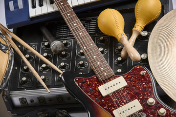 a group of musical instruments including an electric guitar, drum, cymbal, and amplifier