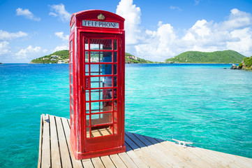 Classic red English telephone booth on a dock in the British Virgin Islands surround by beautiful turquoise Caribbean sea.