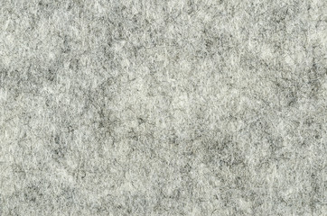 Gray felt surface. Textile material, made of matted synthetic fibers. White, gray and black acrylic pressed together. Fabric pattern. Background. Macro photography from above.