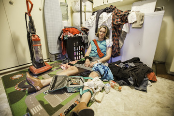 Overwhelmed mom or mother covered in laundry in front of laundry machine