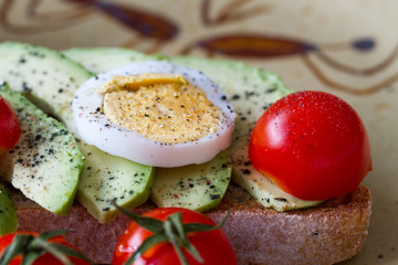 Slice of toast bread with avocado, eggs and cherry tomatoes