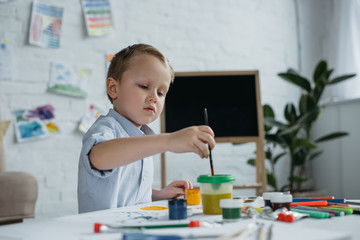 focused little boy with brush and paintings drawing picture alone at home