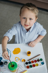 high angle view of little boy with brush and paintings drawing picture alone at home