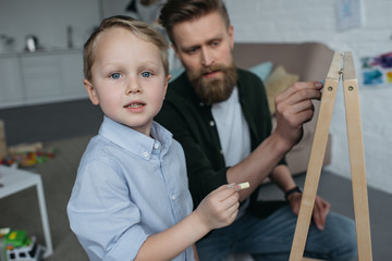 selective focus of little boy and father with pieces of chalk drawing picture on blackboard at home