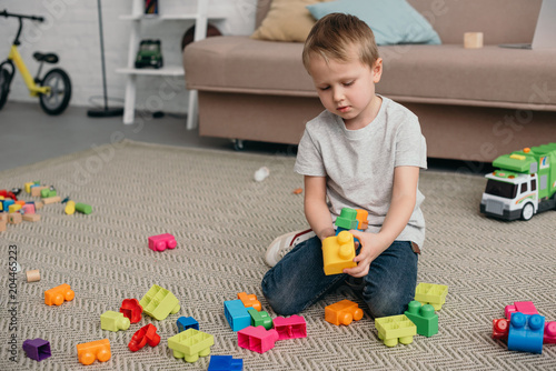 Little Boy Playing With Colorful Blocks On Floor At Home