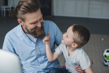 portrait of smiling man and little son looking at each other at home