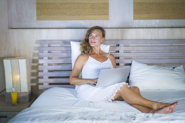 young attractive and beautiful happy woman 30s lying in bed at home using internet working on computer laptop thinking and smiling relaxed thoughtful