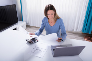 Woman Calculating Invoice With Calculator At Home