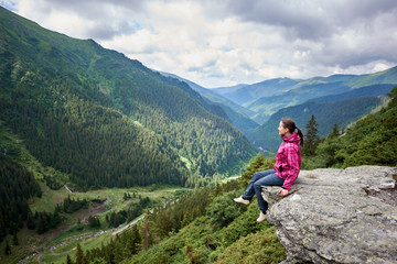 Smiling beautiful female tourist sitting on rock edge admiring breathtaking view of green grassy slopes and mountains with trees, fir trees and pines in Romania. Woman climber happy amazing nature