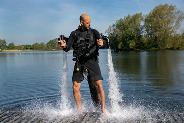 Thrillseeker, water sports lover, athlete strapped to Jet Lev, levitation hovers over lake with blue sky and trees