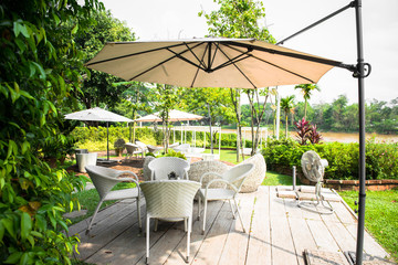 Obraz Outdoor furniture, rattan chairs and glass table on the terrace in the garden. - fototapety do salonu