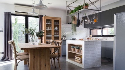 cozy pantry area with natural wood dining table and stainless hanging  shelves in modern vintage style