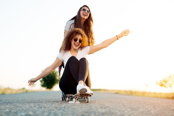 Happy young girl sitting on longboard being pushed by her friend