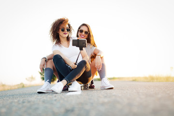 Young women siting together on longboard in road taking selfie