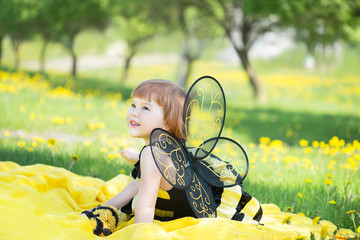 happy little girl in a bee costume walking briskly in a sunny park with dandelions