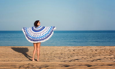 Pretty woman with a mandala round beach tapestry in the ocean coast.