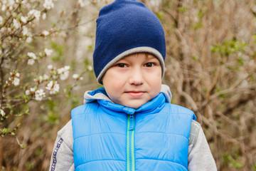 cute little boy in blue cap spring in the garden