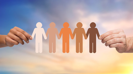population, race and ethnicity concept - multiracial couple hands holding chain of people pictogram over evening sky background
