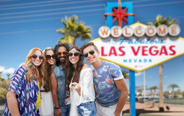 travel, tourism and technology concept - smiling young hippie friends taking picture by smartphone on selfie stick over welcome to fabulous las vegas sign background