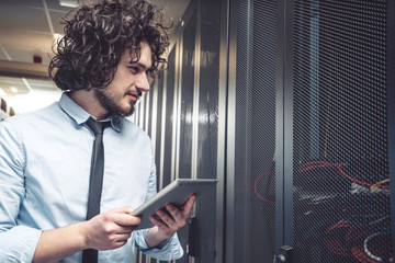 male technician inspecting and working on servers in server room