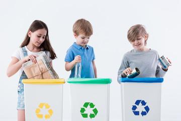 Children segregating paper into bin