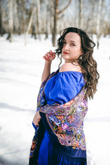 stylish brunette woman with dark hair in a blue dress posing in the open frosty air in a forest among the trees in a traditional Russian wool shawl
