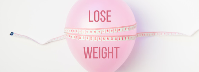 Balloon tied measuring tape on white background. Weight loss, slim body, healthy lifestyle concept. The waist measurement.