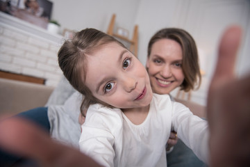 Photographing. Beautiful content mummy and daughter smiling and taking selfies