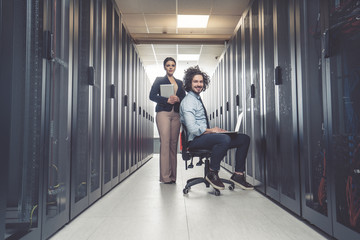 Man and woman working on servers at data center