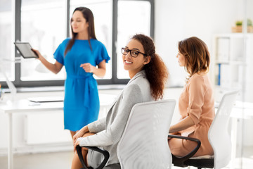 business and people concept - smiling woman at meeting in office