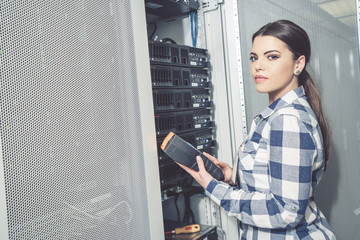 Woman technician working on and inspecting servers in server room