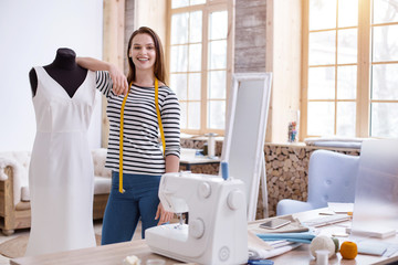 Proud of work. Jovial female designer standing while grinning to camera