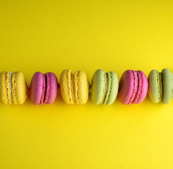 Acrylic Prints Macarons colored baked cakes of almond flour with cream on a yellow background