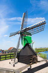 Dutch typical landscape. Traditional old dutch windmill against blue cloudy sky in the Zaanse Schans village, Netherlands. Famous tourism place.