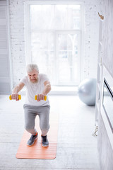 Healthy lifestyle. Charming senior man standing on a yoga mat and doing squats while holding a pair of yellow dumbbells