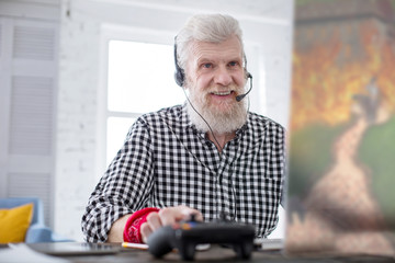Enjoy gaming. Pleasant senior man playing a computer game online and smiling while coordinating his actions with teammates