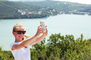 Pre teen girl taking selfie photo on the top of the mountain on the background lake.