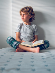 Boy holding book while sitting on bed