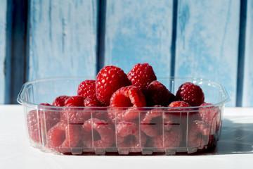 Raspberries in a plastic box