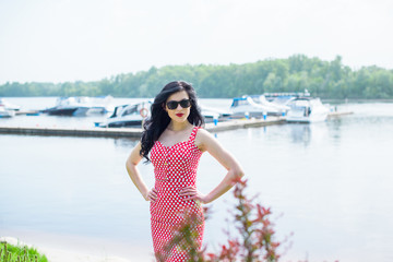 50s vintage style woman at yacht club. Pretty pin-up woman with make-up, vintage style in modern life on vacation wear polka dot dress