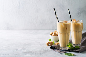 Iced coffee in tall glasses with cream and pieces of sugar, mint and straw