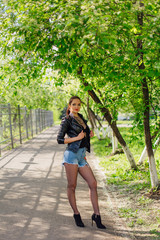 Charming woman dressed in a leather jacket standing on the road